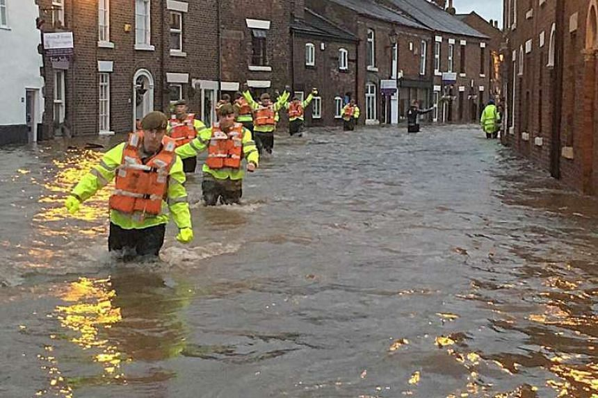 A photo made available by the British Ministry of Defence (MoD) on Dec 27, 2015 of soldiers of the Blenheim Company (2 Lancs) in Ribchester assisting the Emergency Services in conducting warn, inform and evacuation of the local population, on Dec 26,