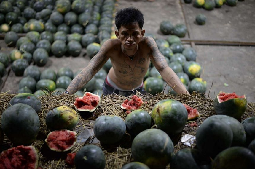 A worker looks at damaged watermelon at a market in Manila on December 27.