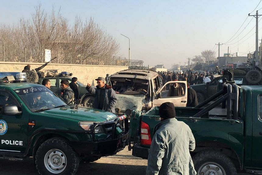 Afghan security members inspect the site of a suicide bomb blast that targeted a foreign forces convoy near Kabul airport, Afghanistan on Dec 28.