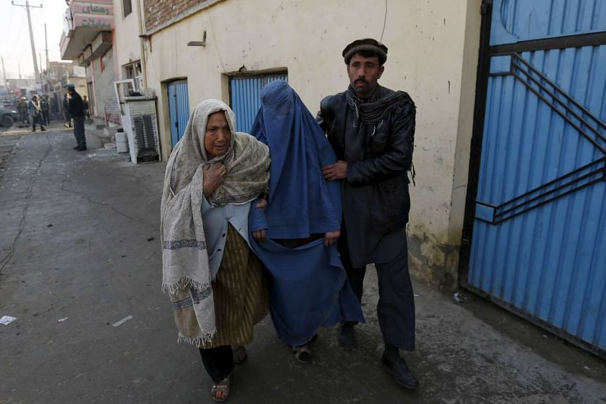 An injured Afghan woman is assisted by her relatives after she was wounded by a suicide attack Kabul, Afghanistan on Dec 28.