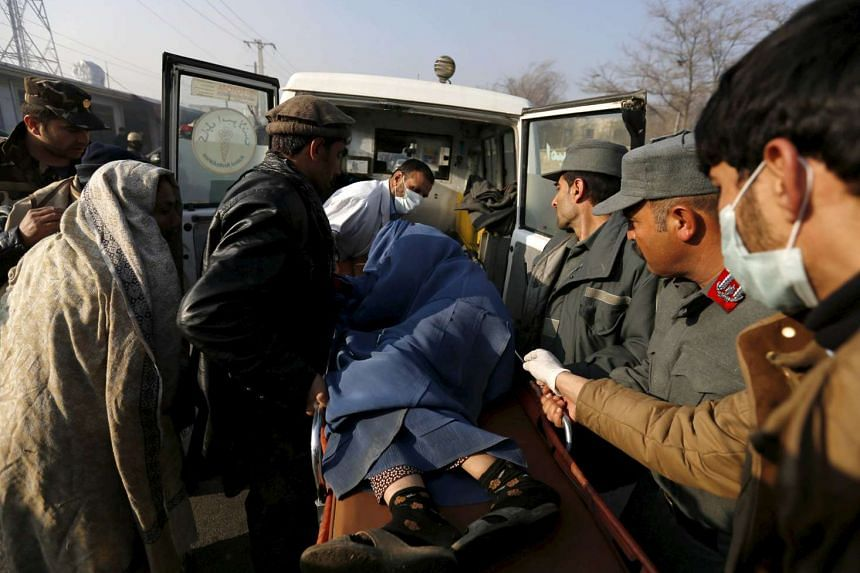 Police and relatives load an injured Afghan woman into an ambulance after she was wounded by a suicide attack in Kabul, Afghanistan on Dec 28.