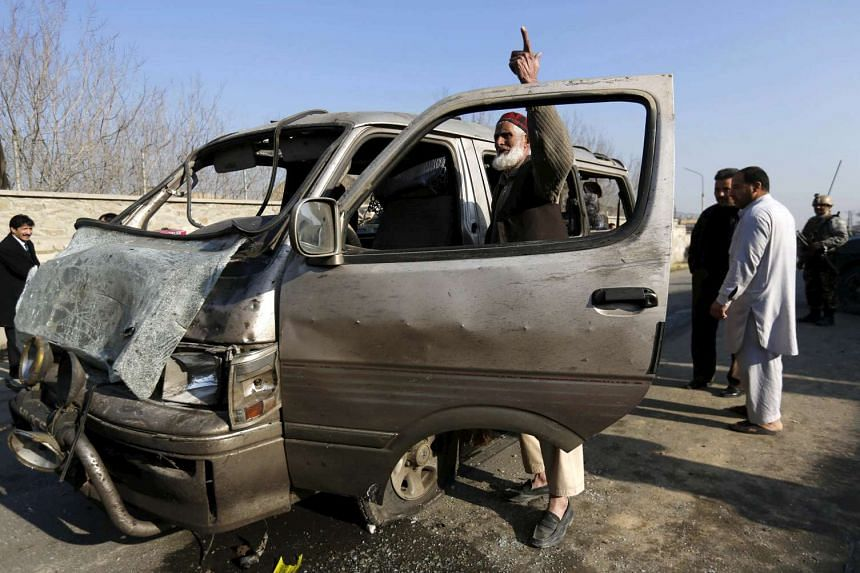 An Afghan man stands next to his damaged vehicle after a suicide attack in Kabul, Afghanistan on Dec 28.