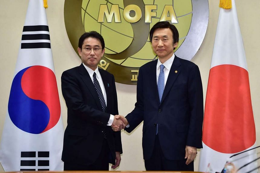 S. Korea's Foreign Minister Yun Byung Se (right) shaking hands with his Japanese counterpart Fumio Kishida during their meeting on Dec 28, 2015.