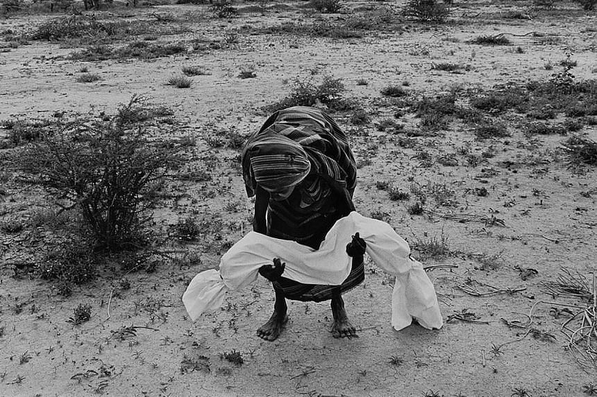 Lifting a dead son to carry him to a mass grave during the famine in Somalia (1992) by James Nachtwey.