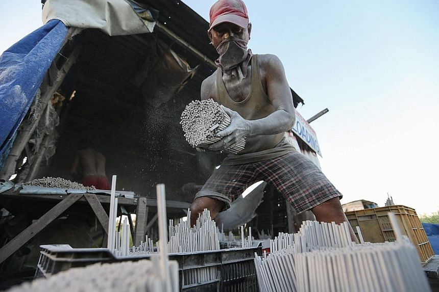 A Filipino worker loading firecrackers in a backyard factory in Bulacan, north of Manila, yesterday. The country's Department of Health has reported more than 50 injuries related to the use of firecrackers from last Monday to Saturday, with the numbe