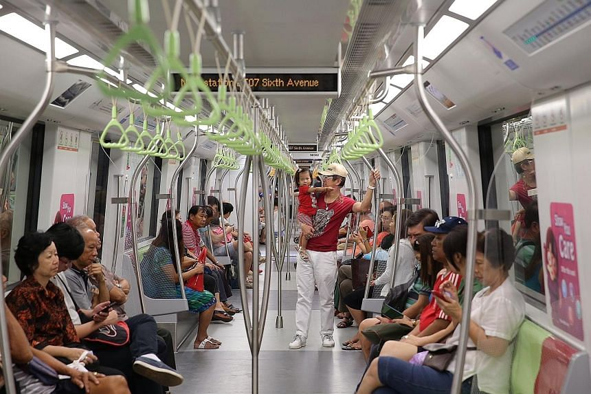 FAST TRACK TO YUMMY TREATS: One-year-old Bella Crystal Ng and her grandfather, Mr James Chan (standing), 65, taking the train to have lunch in Bukit Timah.