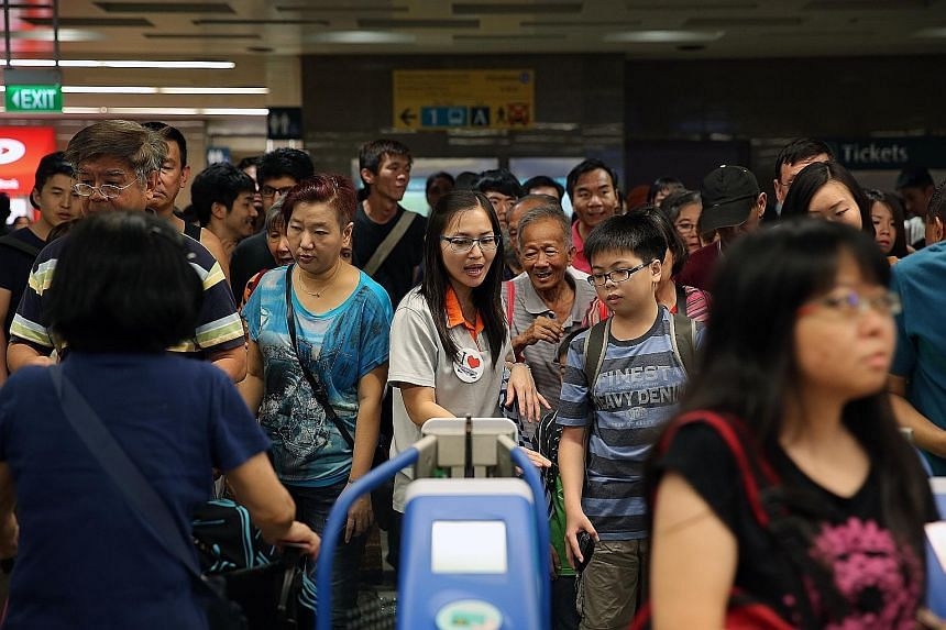 HELPING HAND FOR THE CROWD: An SBS Transit employee (centre) helping commuters as they enter the Beauty World station for an up-close and personal transit experience.