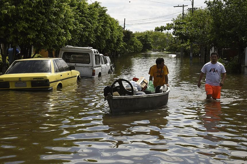 A resident of Asuncion recovering his belongings. About 90,000 people in the area near the Paraguayan capital have been evacuated.