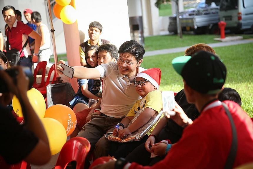 Minister for National Development Lawrence Wong taking a selfie with schoolboy Mohamad Rafael Effendy Razali yesterday after presenting him with a festive gift from his wishlist. The seven-year-old had asked for a backpack after his previous one brok