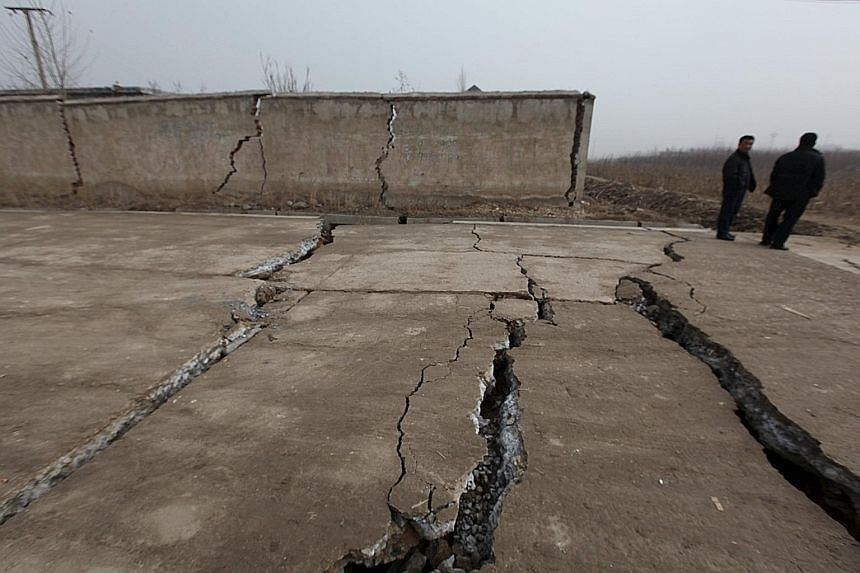 Cracked walls and pavements at the Shandong gypsum mine that caved in on Friday, killing one person and trapping 17. Rescue workers trying to reach survivors yesterday after having drilled a hole through the debris at the Shenzhen industrial park. Mo
