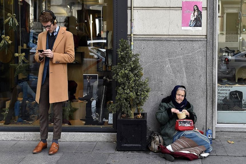 Two faces of Spain - a well-groomed man and a beggar woman. This has been a turbulent year for the euro as the Greek debt crisis once again came to a head and the European Central Bank launched a massive bond-buying programme to breathe life into the