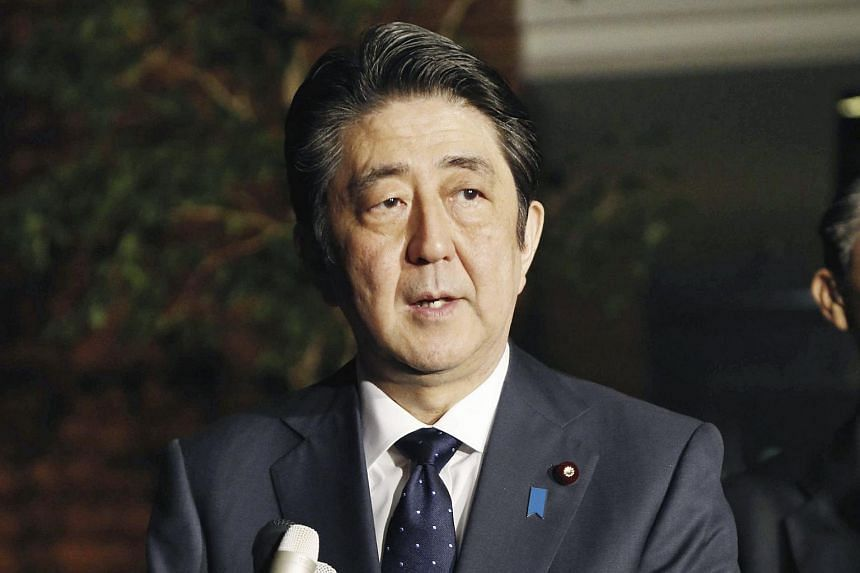 """Japanese Prime Minister Shinzo Abe speaking to reporters after South Korea and Japan reached an agreement on the """"comfort women"""" issue, at the prime minister's office in Tokyo on Dec 28, 2015."""