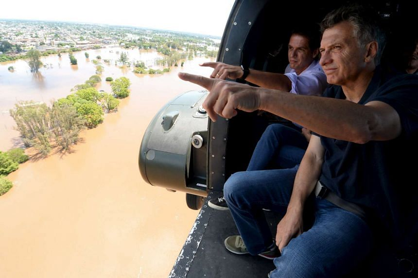 Argentina's President Mauricio Macri (right) looks out of a helicopter during a flight over flood-hit areas in the city of Concordia.