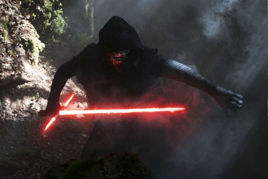 Villain Kylo Ren wielding his cross guard lightsaber in Star Wars: The Force Awakens.