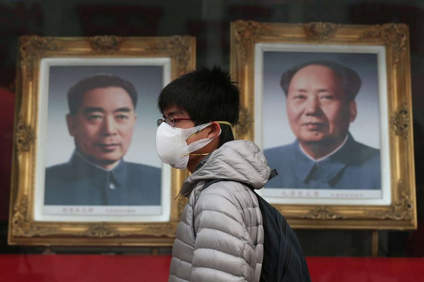 A man walks by portraits of former Chinese leaders Zhou Enlai (left) and Mao Zedong in Beijing on Dec 22, 2015.