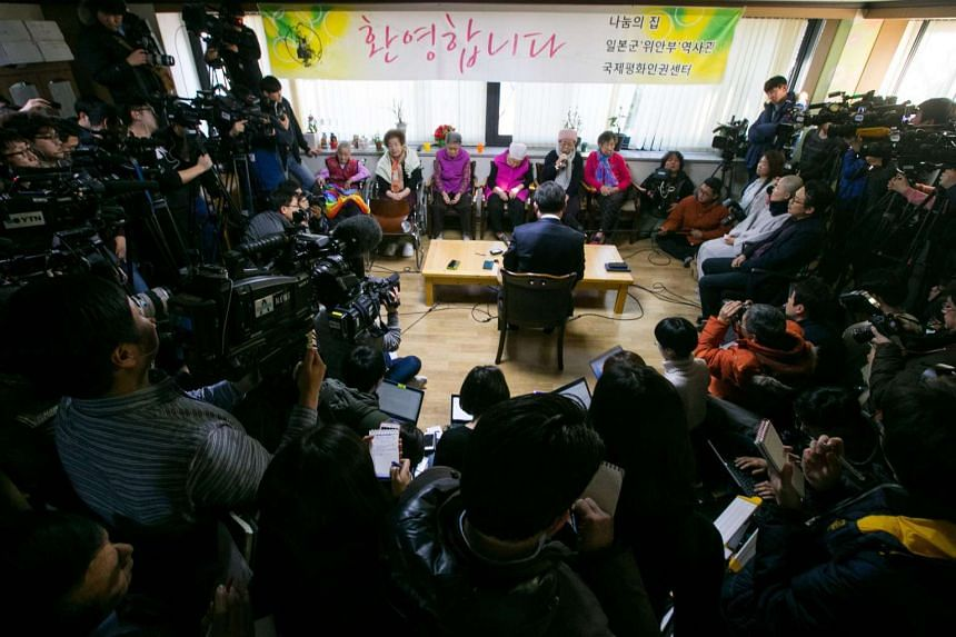 Korean Vice-Foreign Minister Cho Tae Yul (centre) speaking to comfort women victims while surrounded by reporters.