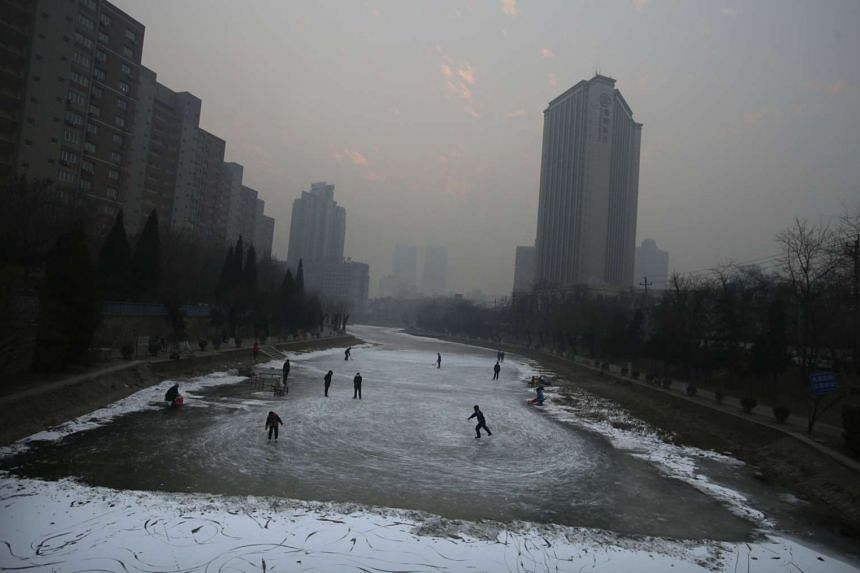 Residents skate and play ice hockey on a frozen river amid heavy smog during winter in Beijing, Dec 29, 2015.