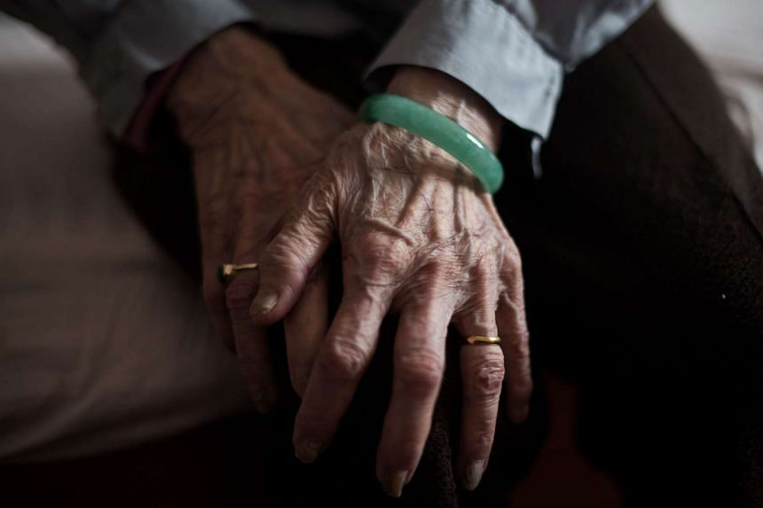 The hands of an elderly Chinese lady as she rests at a care home in China.