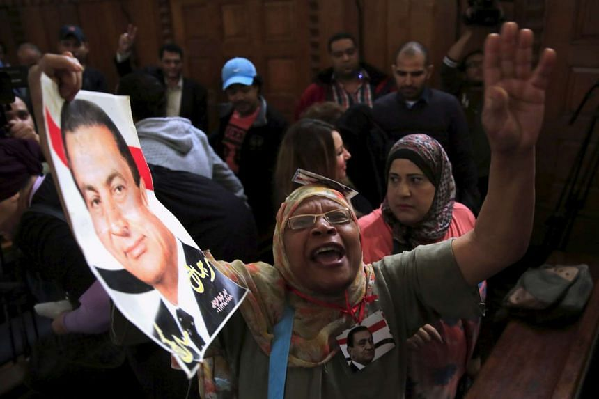 A supporter of former Egyptian President Hosni Mubarak holds his picture as she shouts slogans at the High Court where Mubarak's trial will take place, in Cairo, Egypt, on Nov 5, 2015.