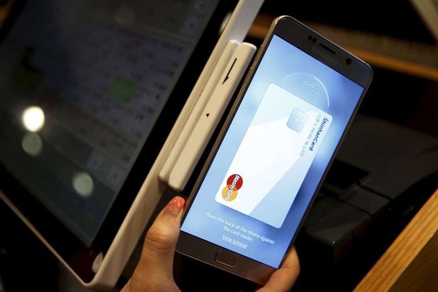 An employee demonstrates using Samsung Pay, Samsung's new mobile payment system at a shop in Seoul, South Korea.