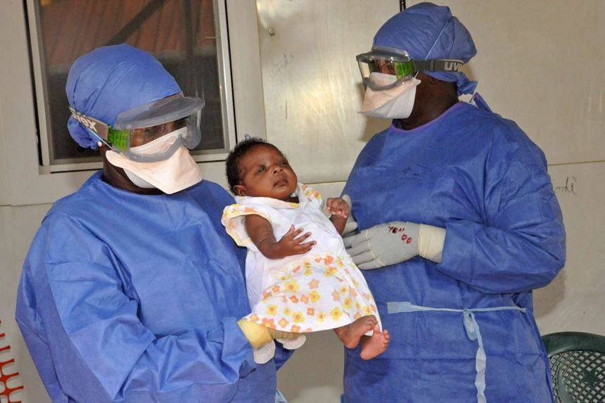 Healthcare workers presenting Noubia, the last known patient to contract Ebola in Guinea, after she was declared treated, on Nov 28, 2015.