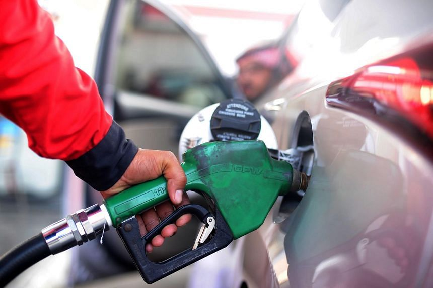 A Saudi employee fills the tank of his car with petrol at a station on Dec 28.