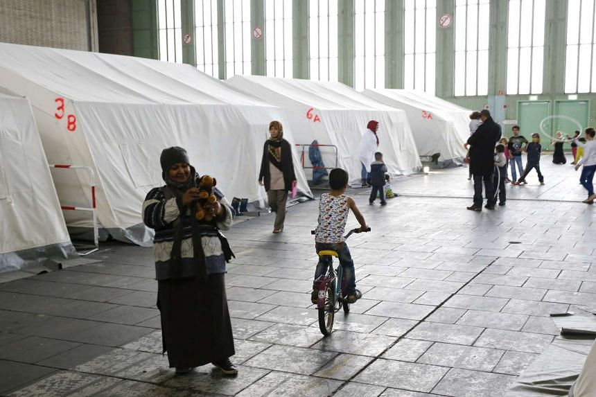 Migrants walk among tents in a refugee shelter in Germany.