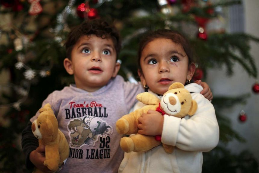Two refugee children from Iraq posing in front of a Christmas tree in Germany on Dec 22.