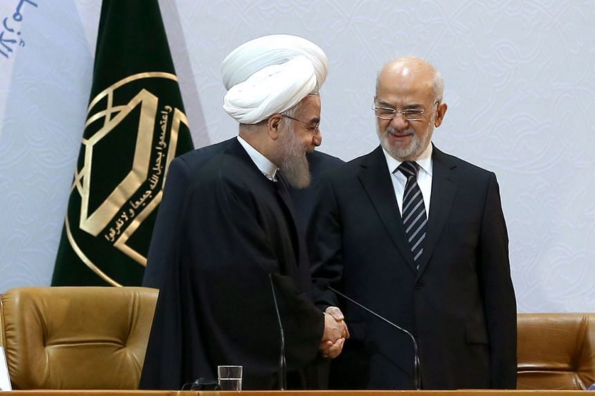 Iranian President Hassan Rouhani (left) shaking hands with Iraqi Foreign Minister Ibrahim Jafari during the 29th International Islamic Conference on Dec 27.