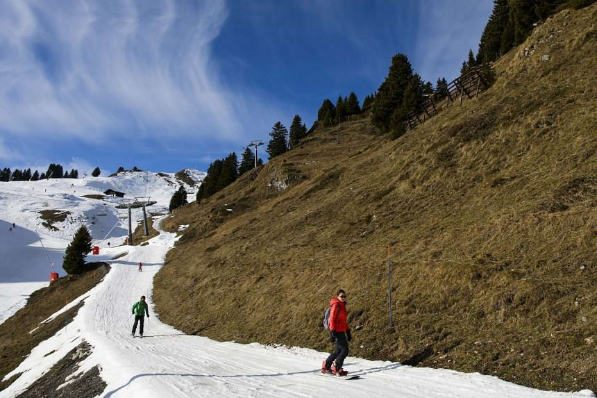 Skiers enjoy the sunny and warm weather at the Villars-Gryon ski resort in Switzerland, on Dec 27, 2015. The warm temperature and dry and sunny weather poses problems for many skiing resorts throughout the alps.