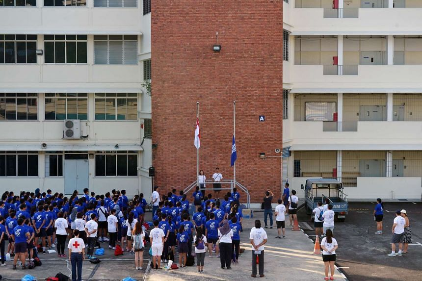 Staff and students of Assumption English School lowering the school flag for the final time at the temporary Queensway premises on Dec 28, 2015.