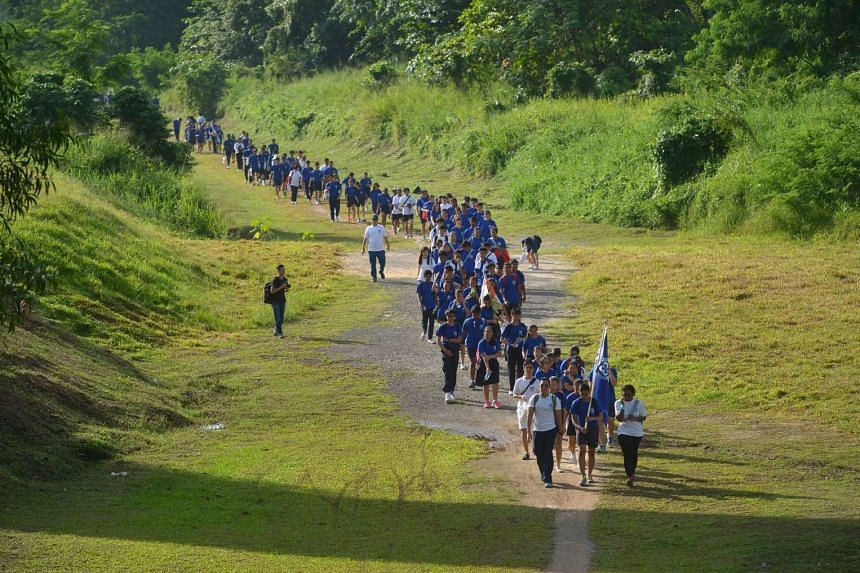 Students and teachers walking along the green corridor during the mass walk to the new school premises.