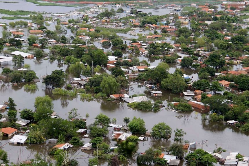 An aerial view of flooded houses in a neighborhood of Asuncion, Paraguay on Dec 28, 2015, for the overflow of Paraguay and Parana rivers. The flood has left 100.000 displaced people who are mostly residing in housing provided by the government.