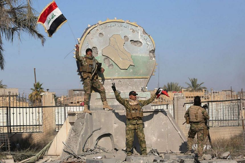 A member of the Iraqi security forces holds an Iraqi flag at a government complex in the city of Ramadi, on Dec 28, 2015.