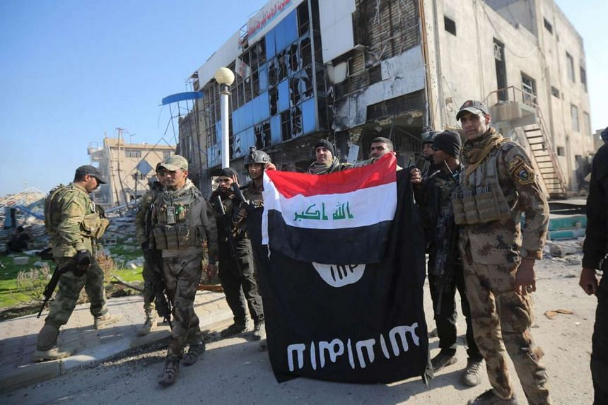 Members of the Iraqi security forces hold an Iraqi flag with an Islamic State flag which they had pulled down in the city of Ramadi on Dec 28.