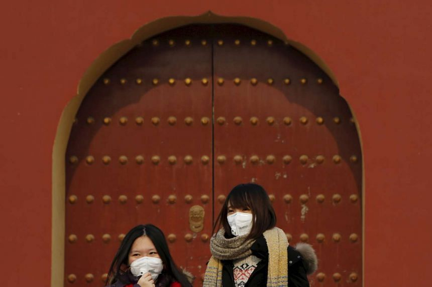 Women wearing protective masks as Beijing braces for four days of choking smog on Dec 19.