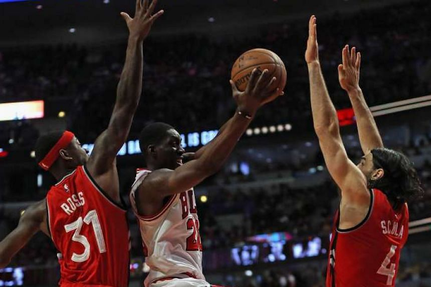 Chicago Bulls forward Tony Snell (centre) driving for a shot between Terence Ross (left) and Luis Scola of the Toronto Raptors at the United Centre on Dec 28, 2015.