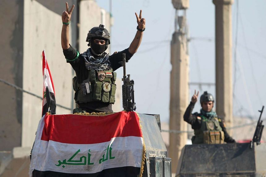 """Members of Iraq's elite counter-terrorism service flash the """"V"""" for victory sign in Ramadi on Dec 29, 2015."""