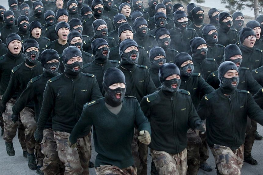 New recruit People's Liberation Army (PLA) soldiers shout slogans during a march in China on Nov 29.