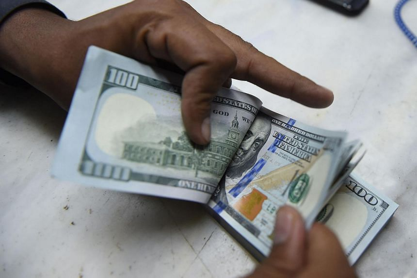 A Pakistani currency dealer counting US dollars at an exchange in Karachi on Dec 17.