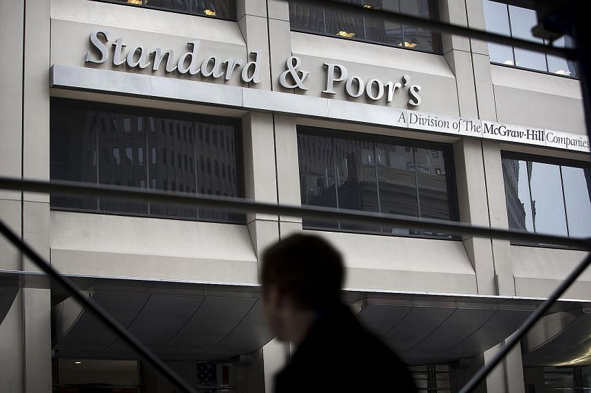 A pedestrian passes in front of Standard & Poor's headquarters in New York on Feb 5, 2013.