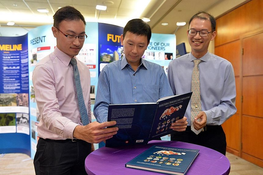 Authors Vincent Pang (left) and Hsu Li Yang (right) with Minister of State for Health Chee Hong Tat at the launch of an SG50 book on Singapore's experience in overcoming infectious diseases.