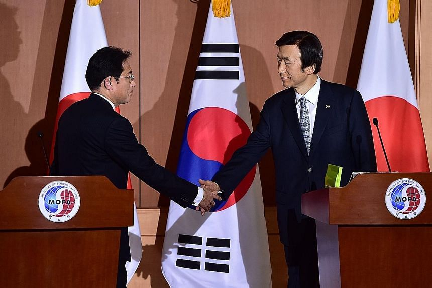 Japan's Foreign Minister Fumio Kishida (far left) and his South Korean counterpart Yun Byung Se after a joint press briefing in Seoul yesterday. Amnesty International said the agreement should not mark the end of the road in securing justice, as some