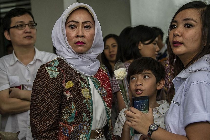Families of Air Asia victims waiting to meet Air Asia management at a local police headquarters in Surabaya yesterday. A private service was held in the city as a memorial to those aboard Flight QZ8501.