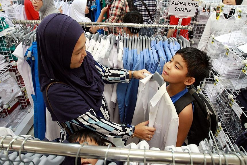 A woman in Malaysia shopping with a child for a new school uniform before the new term starts. Johor's Sultan Ibrahim Ismail says he is worried that English is becoming a language for the old in Malaysia as the young are not being taught the language