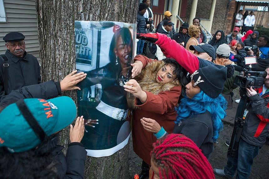 The daughters of Ms Bettie Jones, along with friends and supporters, displaying a picture of her during a vigil outside the family home in Chicago on Sunday.