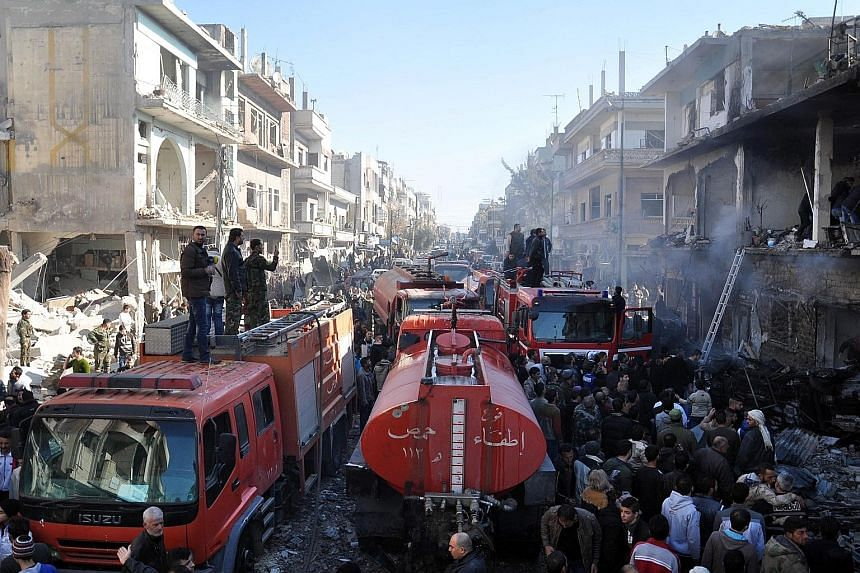 Fire engines at the site of two car bomb attacks in the Al-Zahraa neighbourhood in Homs yesterday. The attack came less than three weeks after the Islamic State in Iraq and Syria militant group claimed responsibility for explosions in the same neighb