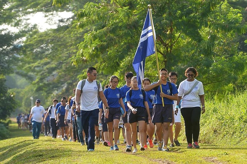 Assumption English School students, led by their teachers, Mr Rene Loh (at left) and Ms Bhavaniswari Batumalia (far right), walked 6km from Queensway to their newly rebuilt school in Bukit Timah yesterday. The new school year starts on Monday. The sc
