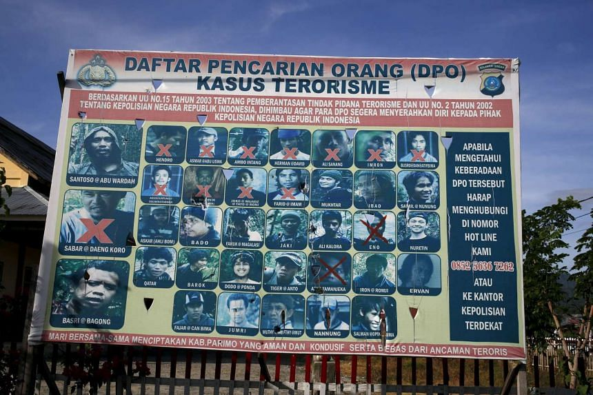 A police billboard showing a list of individuals wanted in relation with terrorism cases in Sulawesi, Indonesia.