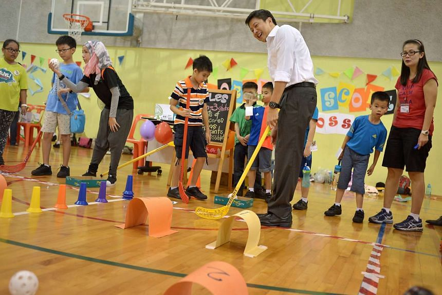 Acting Minister for Education Ng Chee Meng trying a game organised by pupils from Frontier Primary's Red Cross CCA on Oct 8, 2015.